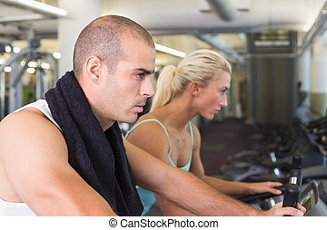 Determined fit couple working on exercise bikes at gym -...