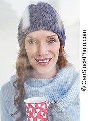 Pretty redhead in warm clothing holding mug seen through...
