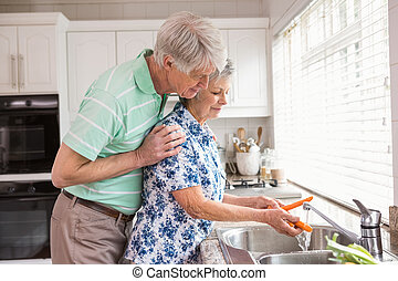 Senior couple washing vegetables at sink at home in the...
