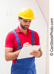Construction worker taking notes on clipboard in a new house