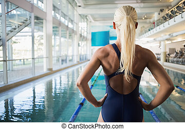 Rear view of fit female swimmer by pool at leisure center