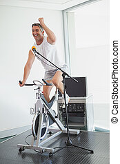 Spinning instructor motivating his class at the gym