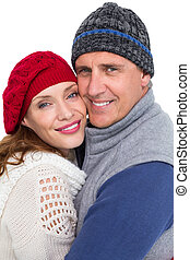 Happy couple in warm clothing hugging on white background