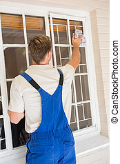 Rear view of handyman cleaning the window in a new house