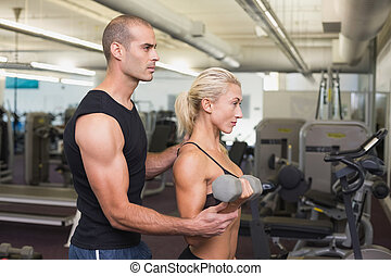 Male trainer assisting woman with dumbbell in gym
