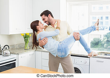 Young couple having fun together at home in the kitchen