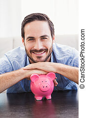 Smiling man laying on the piggy bank