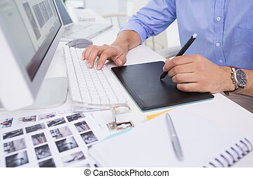 Graphic designer using digitizer at his desk in creative...