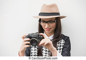 Pretty hipster looking at her camera