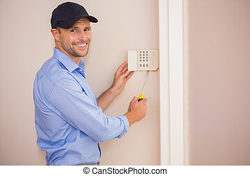 Smiling handyman fixing an alarm system on the wall