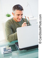 Smiling man holding glasses and using laptop in his office