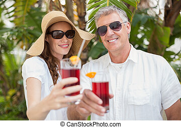 Holidaying couple toasting with cocktails in a green park
