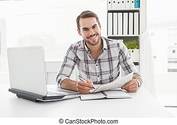 Casual businessman writing on newspaper in his office