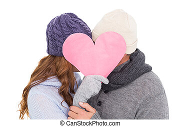 Couple in warm clothing holding heart on white background