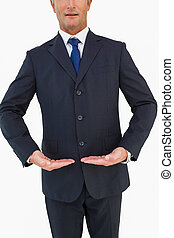 Mid section of a businessman in suit with hands out on white...
