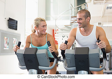 Fit couple working on exercise bikes at gym - Portrait of a...