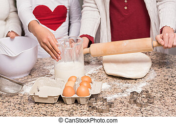 Multi-generation family baking together at home in the...