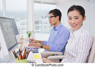Creative team working at desk in creative office