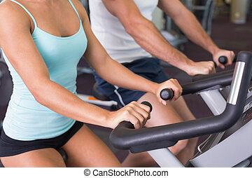 Mid section of couple working on exercise bikes at gym - Mid...