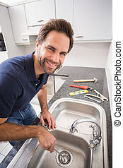 Plumber fixing sink with screwdriver in the kitchen