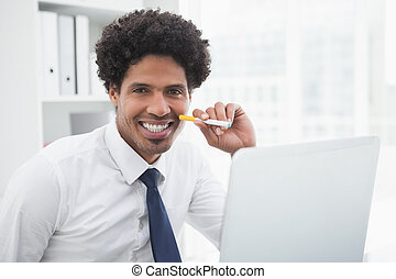 Portrait of a smiling businessman holding cigarette in his...
