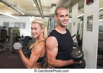 Couple exercising with dumbbells in gym - Side view of a...