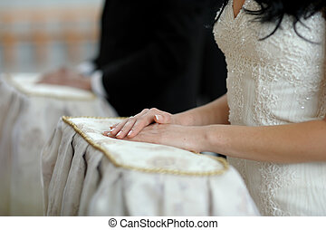 Nice brides hands close-up during wedding church ceremony -...