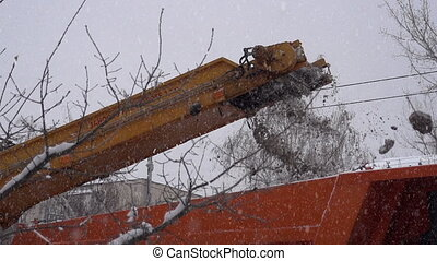 Snowplows in action. Snow falls from the conveyor belt in...