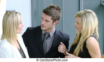 Businessman and two businesswomen talking
