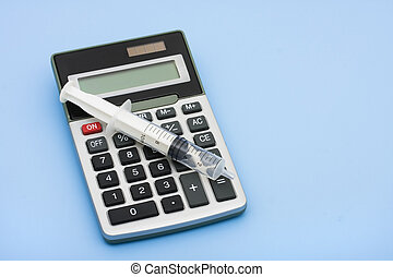 Calculating Healthcare Costs - A calculator and a syringe on...