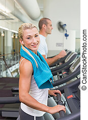 Fit young couple running on treadmills at gym - Side view of...