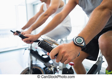 Mid section of men working on exercise bikes at gym - Close...