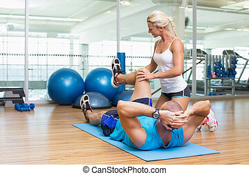 Trainer assisting man with exercises at fitness studio