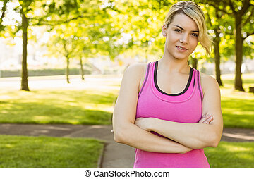 Fit blonde smiling at camera in the park on a sunny day