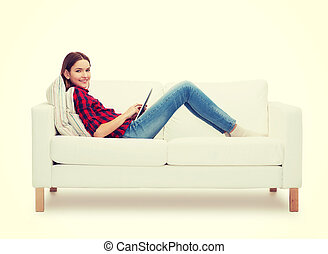 teenage girl sitting on sofa with tablet pc - home, leisure,...