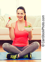 smiling teenage girl with green salad at home - healt,...