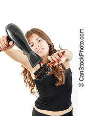 Young woman with blow dryer and hairbrush working as...