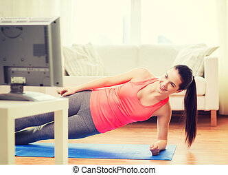 smiling teenage girl doing side plank at home