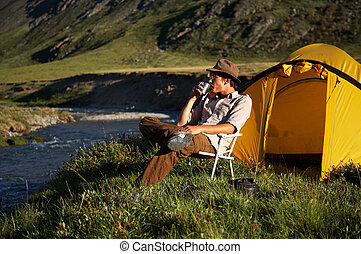 man is sitting in the chair at the camp in mountains near...