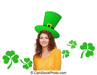 smiling teen girl in green top hat with shamrock - gestures,...