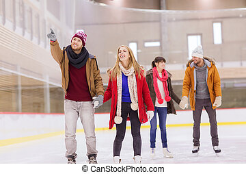 happy friends pointing finger on skating rink - people,...