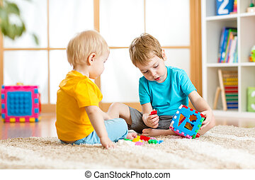 two little boys play together with educational toys - two...