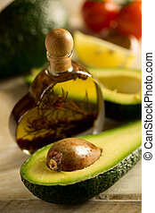 avocado - Bottle of avocado essential oil with fresh avocado...