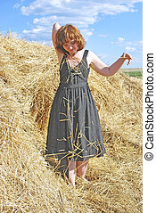 haystack and young woman on distant plan