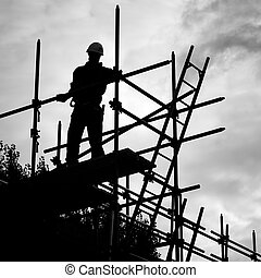 silhouette construction worker on scaffolding building site...