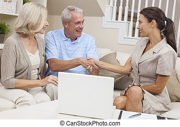Saleswoman Shaking Hands With Senior Couple at Home - A...
