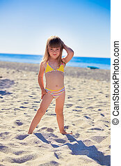 Funny girl on a beach - Funny little girl wearing swimsuit...