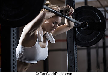 Tired girl after weight lifting - View of tired girl after...