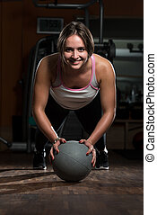 Young Woman Exercising Push Ups On Medicine Ball -...