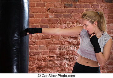 Punching the bag - Young strong screaming woman punching the...